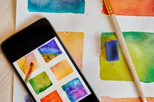 smartphone on arts hand drawn background with artist supplies