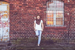 Girl leaning against brick wall