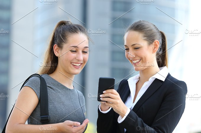 Two businesswomen talking about smart phone.jpg - Business