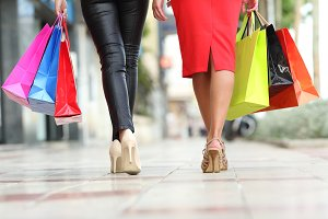Two fashion women legs walking with shopping bags.jpg