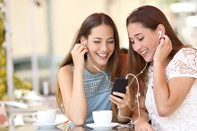 Friends sharing and listening to music with smartphone.jpg