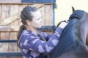 girl braiding a horse mane