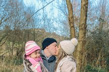 Couple with happy daughter kissing
