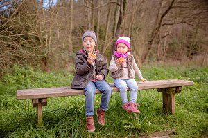 Boy and little girl eating in bench