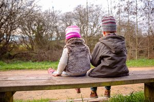 Boy and little girl sitting in bench
