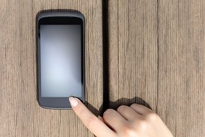 Finger pressing a blank smart phone touch screen.jpg