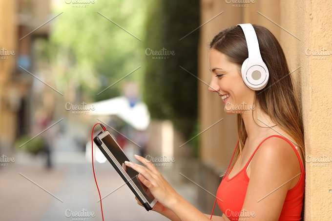 Girl browsing a tablet and listening with headphones.jpg - Technology