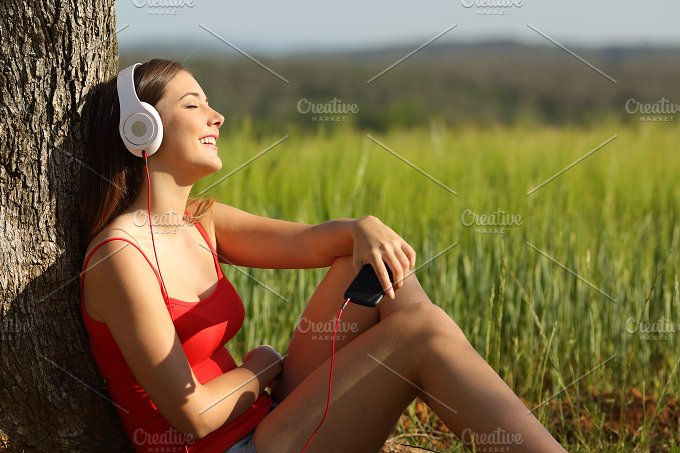 Girl listening to the music relaxed in a green field.jpg - Technology