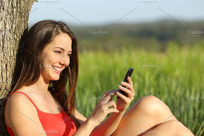 Girl texting in a smart phone relaxed in the country.jpg - Technology