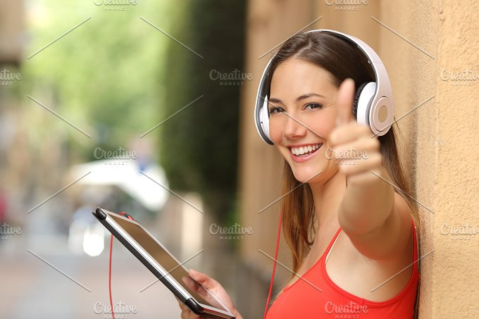 Girl with thumbs up using a tablet with headphones.jpg - Technology