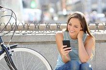 Happy girl watching media in a smart phone.jpg