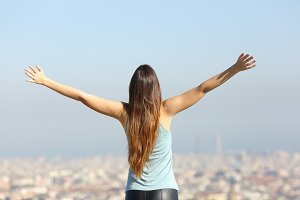 Happy tourist woman raising arms looking at the city.jpg