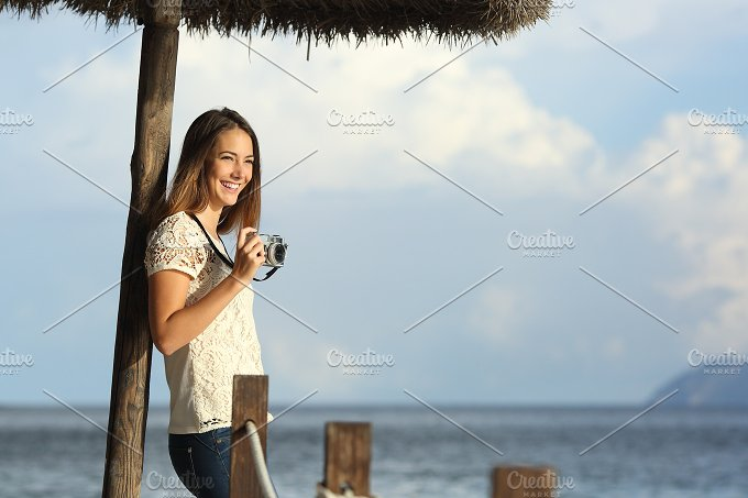 Happy photographer photographing in the beach.jpg - Holidays