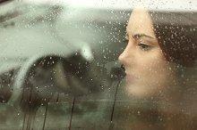 Sad woman looking through a car window.jpg