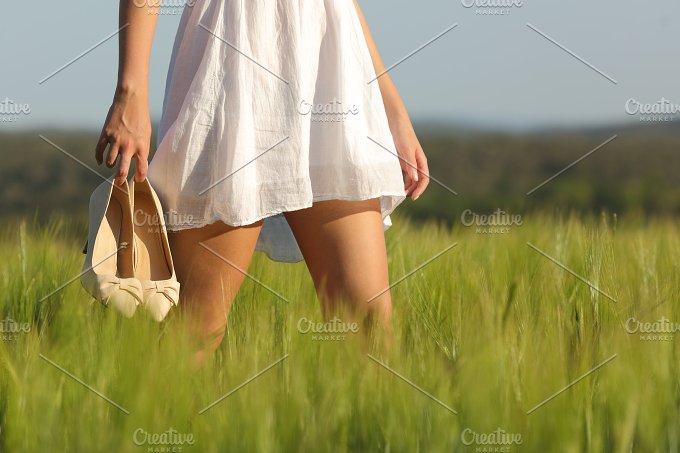 Relaxed woman legs walking in a field in summer.jpg - People