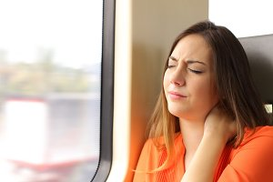 Stressed woman with neck ache in a train wagon.jpg