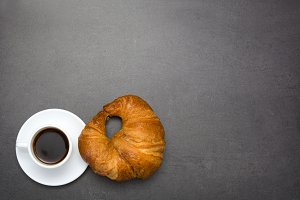 Coffee and croissant on slate table