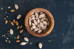 Wooden bowl of salty almond nuts