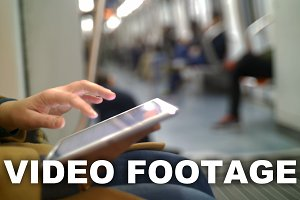 Woman in subway train using tablet