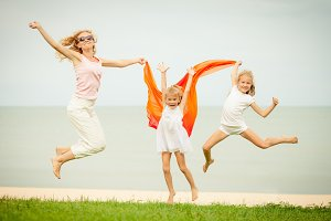 Happy family jumping on beach