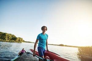 Young man carrying a kayak