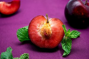 Colorful halved plum with mint