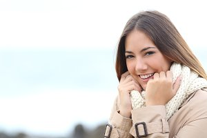 Beauty woman smiling and grabbing her scarf in winter.jpg