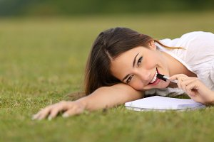 Candid happy woman lying on the grass writing.jpg