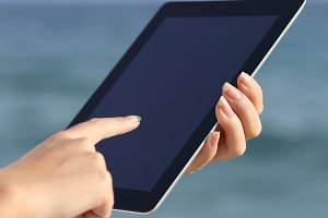 Close up of a woman hands holding and browsing a digital tablet on the beach.jpg