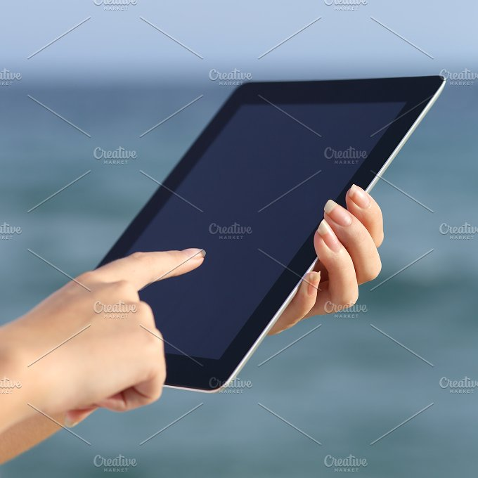 Close up of a woman hands holding and browsing a digital tablet on the beach.jpg - Technology