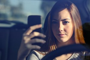 Front view of a woman driving a car and typing on a smart phone.jpg