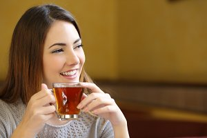 Happy woman holding a cup of tea in a coffee shop.jpg