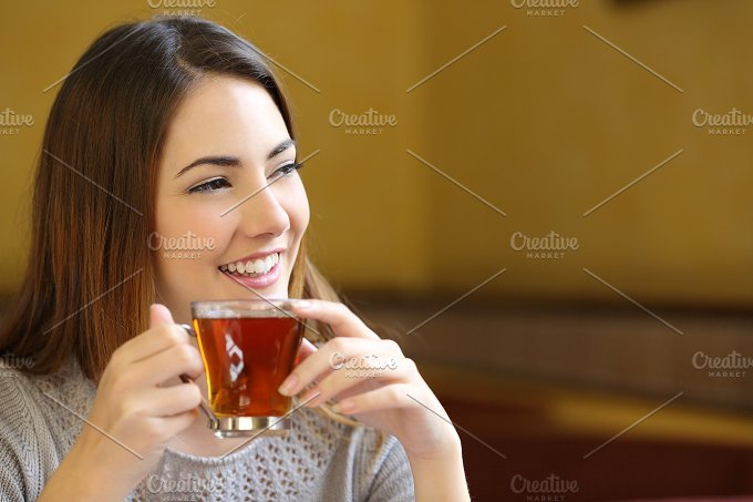 Happy woman holding a cup of tea in a coffee shop.jpg - Food & Drink