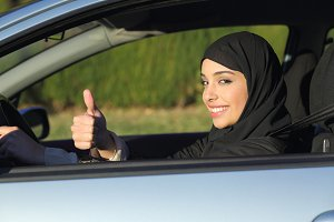 Happy arab saudi woman driving a car with thumb up.jpg