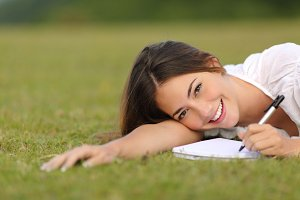 Happy woman lying on the grass and writing in a notebook.jpg