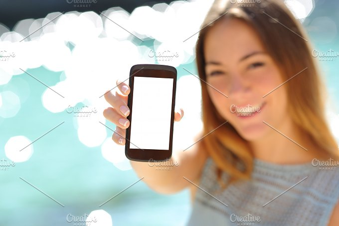 Happy woman showing a blank smartphone on the beach.jpg - Technology