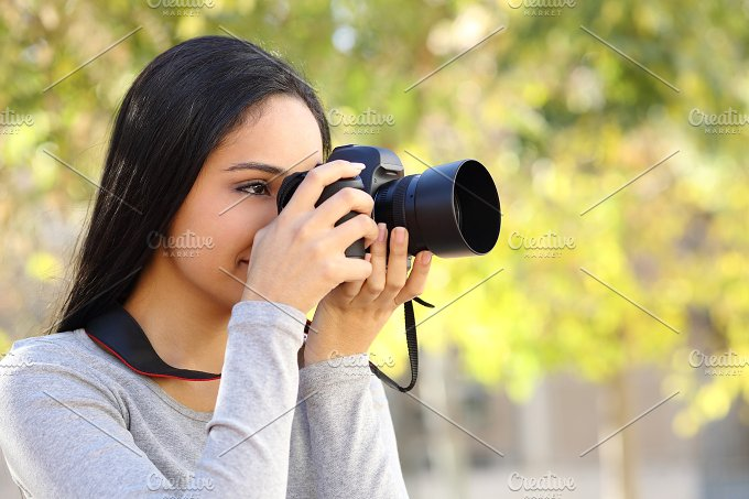 Photograph woman learning photography in a park.jpg - Technology
