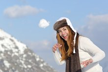 Playful woman throwing a snow ball in winter on holidays.jpg