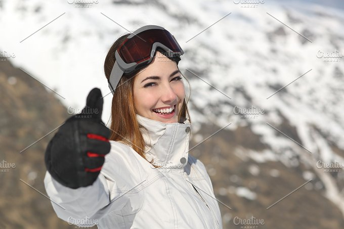 Positive skier woman gesturing thumb up in winter.jpg - Sports