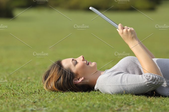 Profile of a happy woman reading a tablet reader on the grass.jpg - Technology