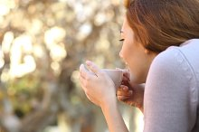 Relaxed woman holding a cup of coffee outdoor.jpg