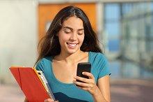 Student teenager girl walking while looking her smart phone.jpg