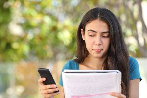 Teenager student girl looking sideways at mobile phone while studying.jpg