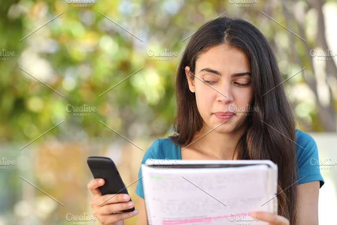 Teenager student girl looking sideways at mobile phone while studying.jpg - Education