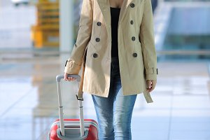 Traveler woman walking carrying a suitcase in an airport.jpg