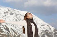 Woman breathing fresh air raising arms in winter.jpg