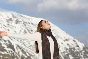 Woman breathing fresh air raising arms in winter.jpg