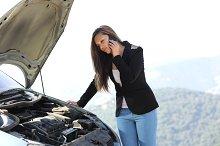 Woman on the phone looking her crash breakdown car.jpg