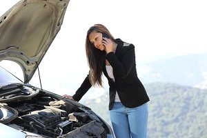 Woman on the phone looking her crash breakdown car.jpg