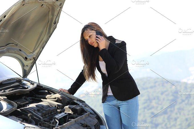 Woman on the phone looking her crash breakdown car.jpg - Transportation